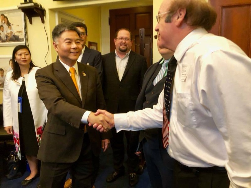 CEO Chip Ahlswede in the background as President Steve Drust shakes Rep. Ted Lieu's hand.